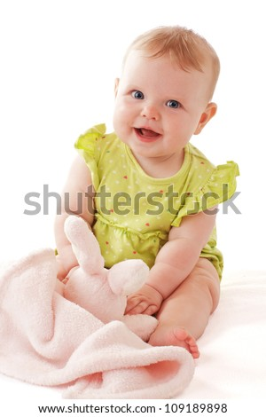 Laughing baby girl with big blue eyes wearing a lime green dress sits and plays with a soft bunny blanket. Pastels, isolated on white background, vertical, copy space.