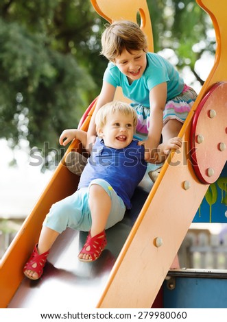 laughing   baby girls  on slide at playground area in summer - stock photo