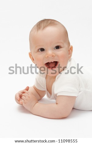 Laughing baby lying on the floor - stock photo