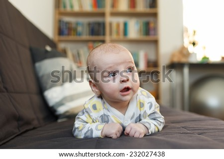 laughing baby on sofa, Beautiful smiling cute baby, expressive adorable happy child in childroom  - stock photo
