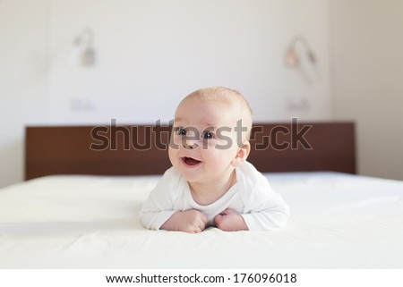laughing baby on sofa, Beautiful smiling cute baby, expressive adorable happy cute - stock photo