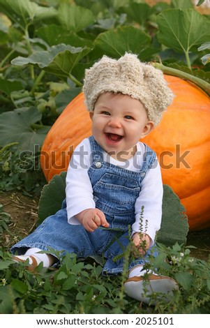 laughing baby sitting with a pumpkin - stock photo