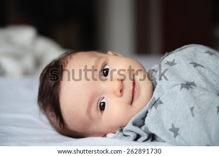 Laughing baby.Small baby crawling on the bed in white room.On his face interest and wondering.European.Baby surprised. - stock photo