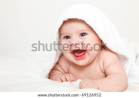Laughing baby with towel - stock photo