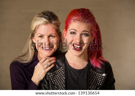 Laughing beautiful European mother and daughter indoors - stock photo