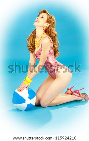 Laughing beautiful girl pin-up in a pink bikini with beach ball - stock photo