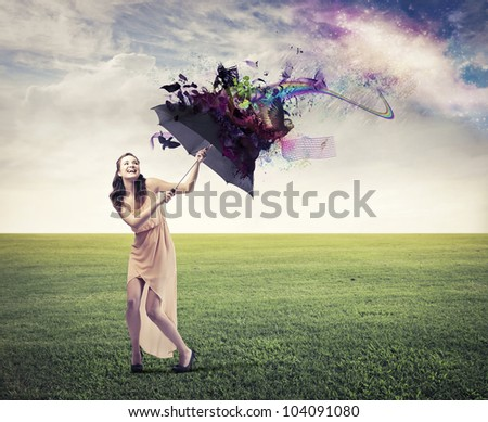 Laughing beautiful woman on a green meadow sheltering from the rainbow under an umbrella - stock photo