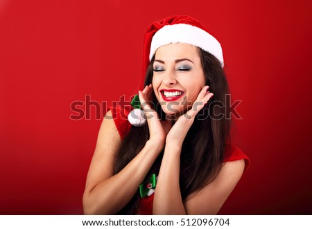 Laughing beautiful woman with toothy smile in santa claus christmas costume on bright red background.