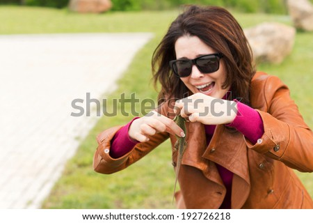Laughing beautiful young woman wearing sunglasses standing holding a lizard in her hands alongside a rural lane - stock photo