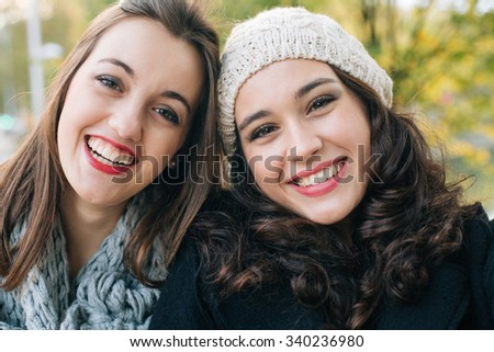 Laughing best friends posing for a selfie outdoors in autumn - stock photo