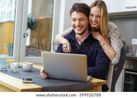 Laughing blond woman in dotted blouse leaning on attractive bearded smiling man using laptop at table in kitchen - stock photo