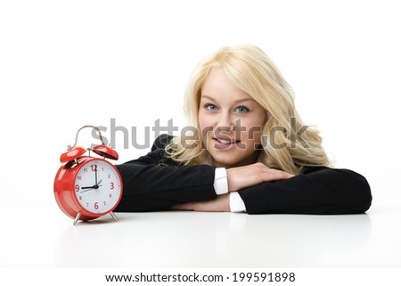 Laughing blond woman with red alarm clock