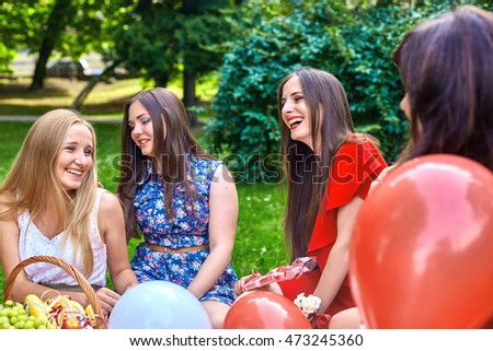 Laughing blonde and brunette women sit in the park