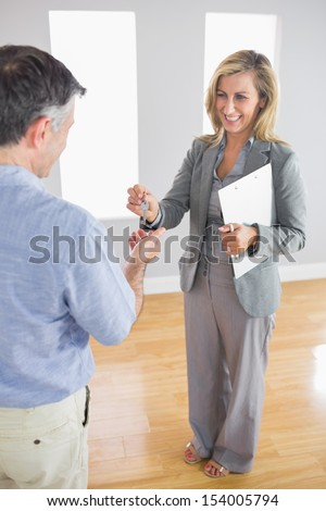Laughing blonde realtor holding a briefcase and giving a key to a mature buyer in an empty room - stock photo