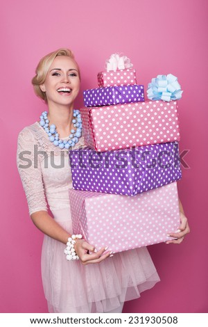 Laughing blonde woman holding big and small colorful gift boxes. Soft colors. Christmas, birthday, Valentine day, presents. Studio portrait over pink background - stock photo