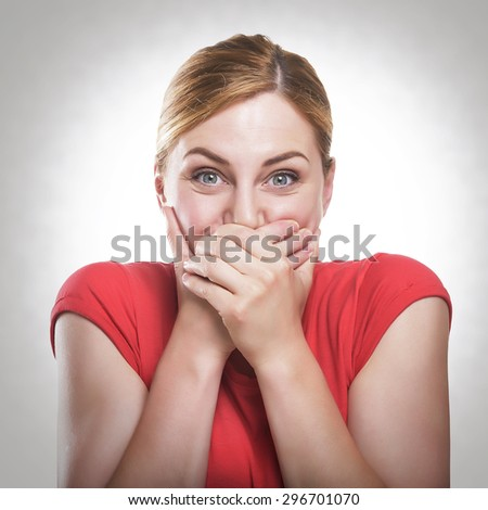 Laughing blonde woman in red t-shirt covers mouth with hand, toned photo. - stock photo