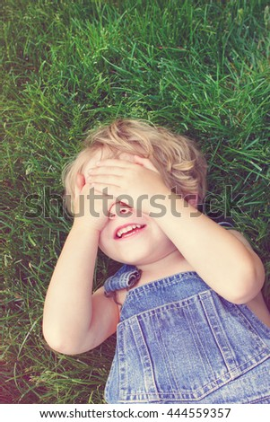 Laughing boy covering his eyes