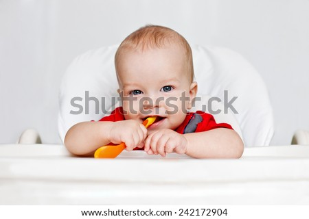 laughing boy holding a spoon on a white background - stock photo