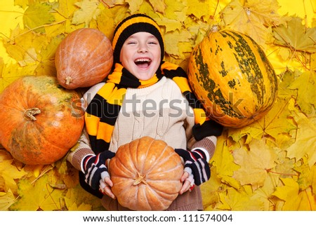 Laughing boy lies on yellow leaves - stock photo