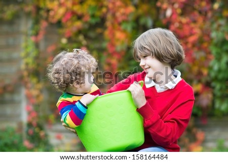 Laughing boy playing with his little baby sister in a laundry basket - stock photo