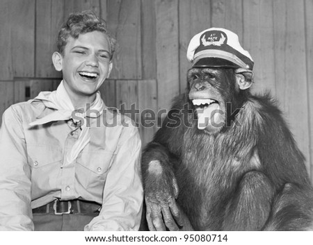 Laughing boy scout and monkey wearing hat - stock photo
