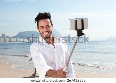 Laughing brazilian man making picture at Copacabana beach - stock photo