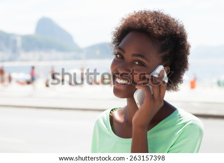 Laughing brazilian woman at Rio de Janeiro at phone - stock photo