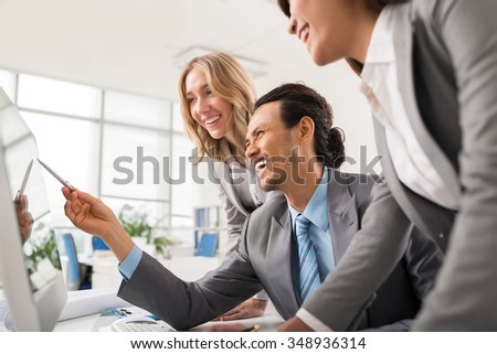 Laughing business people looking at computer monitor