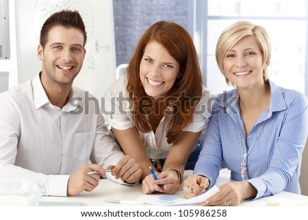 Laughing business team posing in office, smiling at camera. - stock photo