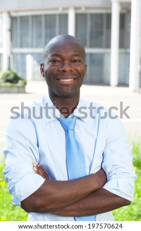 Laughing businessman from Africa with crossed arms - stock photo