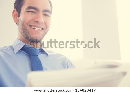 Laughing businessman looking at camera and reading a newspaper on yellow background