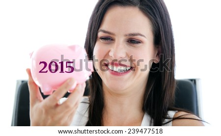 Laughing businesswoman holding a piggybank against 2015 in grey - stock photo