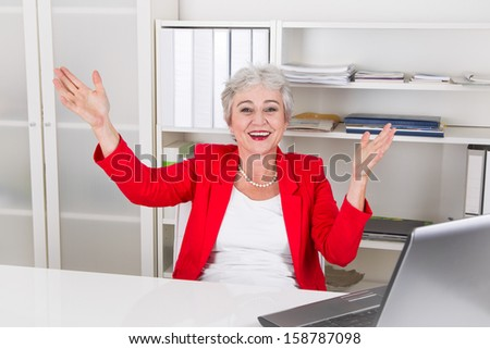 Laughing businesswoman in red sitting at desk with raised arms - stock photo