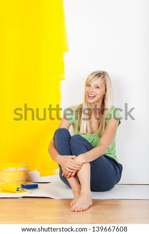 Laughing casual barefoot young woman taking a break from painting sitting on the floor with a half painted yellow and white wall behind her showing the before and after colours