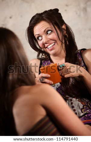 Laughing Caucasian brunette female sitting with friend indoors - stock photo