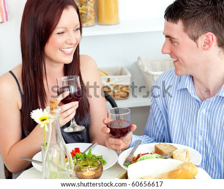 Laughing caucasian couple having dinner at home in the kitchen - stock photo