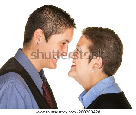Laughing Caucasian lesbian couple facing each other - stock photo