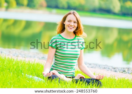 laughing cheerful girl in lotus position on the lake - stock photo