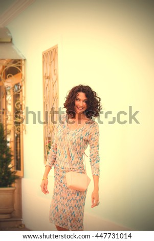 laughing cheerful middle aged brunette with a handbag near the white wall of an old building. woman in a summer dress for a walk. instagram image filter retro style - stock photo