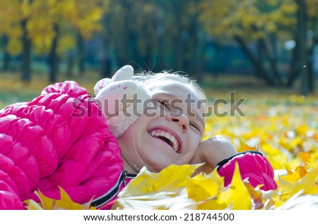 Laughing child enjoying herself while lying on autumnal ground - stock photo