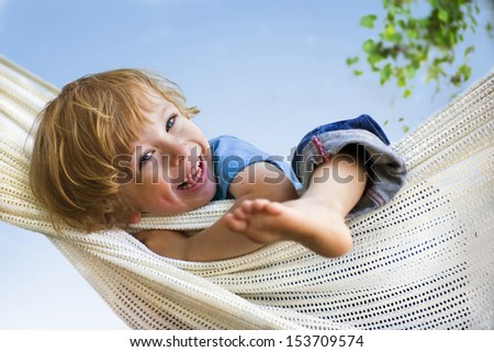 Laughing child in hammock  - stock photo