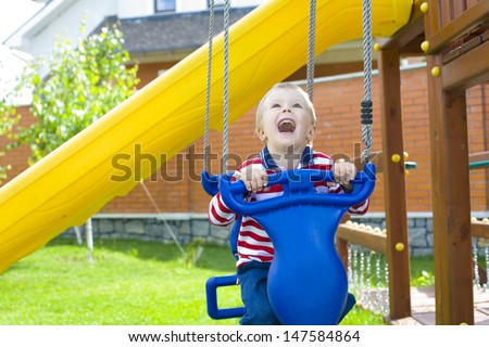 laughing child on a swing - stock photo