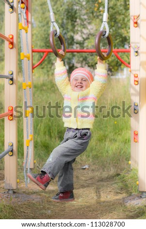 Laughing child on sports rings in autumn park