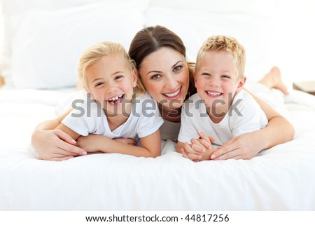 Laughing children playing with their mother lying on a bed at home