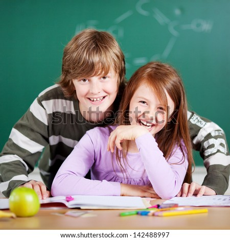 Laughing children posing over the blackboard background