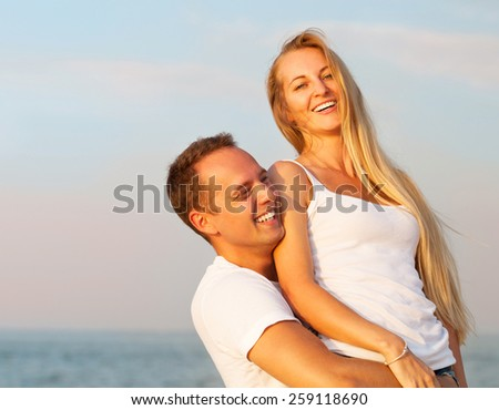 Laughing couple enjoying nature over sea background. Attractive man and woman at the beach. Summer Vacation