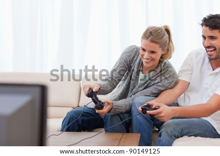 Laughing couple playing video games in their living room - stock photo