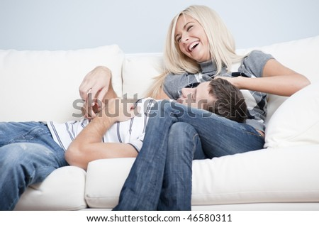 Laughing couple relaxing on couch, with man lying with his head in the woman's lap. Horizontal format. - stock photo