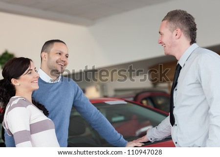 Laughing couple talking with a salesman in a car shop