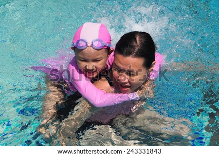 Laughing cute daughter playing and swimming with her mother at the pool